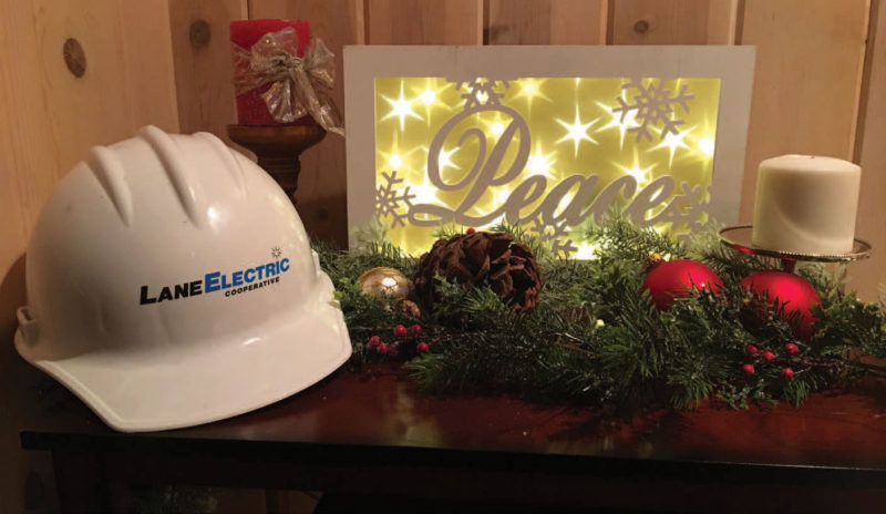 """A Lane Electric hat next to an illuminated decorative sign reading """"Peace"""""""