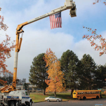 A lift truck hangs an American flag from the lift arm