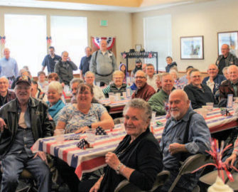 veterans sit at tables watching musical performance