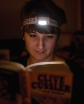 Woman wearing headlamp and reading book