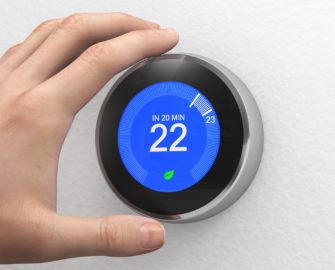 "hand adjusting a digital ""smart"" thermostat"
