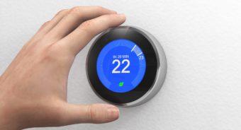 """hand adjusting a digital """"smart"""" thermostat"""