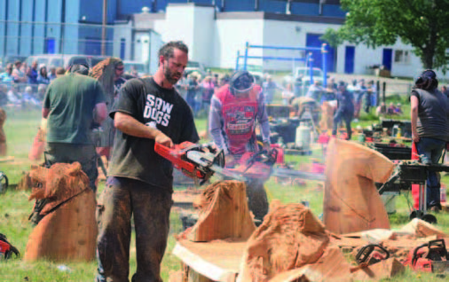 Photo of man carving wood into chainsaw art