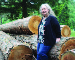 Photo of Peggy Pantel leaning on a pile of logs