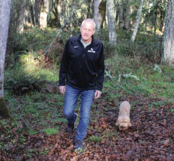 Chris Seubert and dog walking in the woods