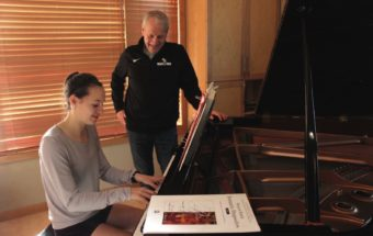 Chris Seubert listening to daughter, Hannah, play piano