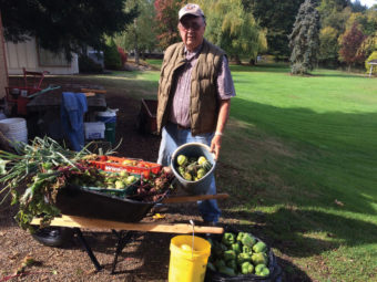 Hugh Buermann standing next to buckets of vegetables, in his yard