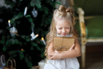 little girl holding present by Christmas tree