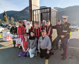Volunteers from Oakridge and Springfield gather at the Mrs. Santa in Jail fundraiser for the Toys for Tots program. Mike Cameron, right, and Leo Robb, second from right, are members of the Oakridge board for Toys for Tots. The event was held in the parking lot of Ray's Food Market in Oakridge.