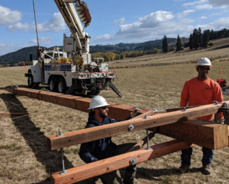 Linemen prepare a glulam pole for use