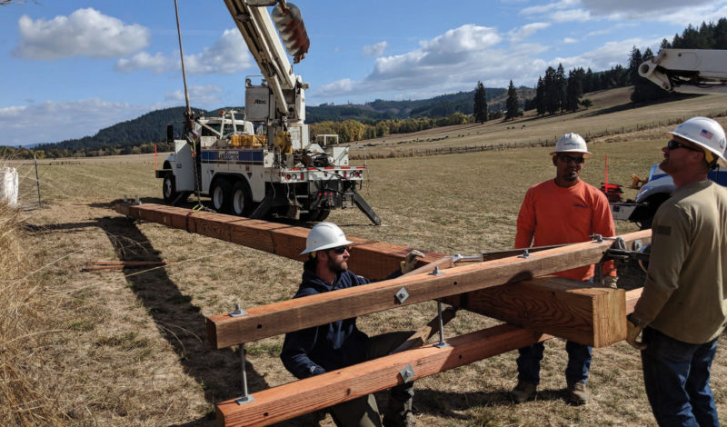 Linemen prepare a glulam pole for use