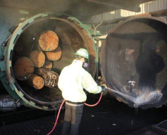 McFarland Cascade employee preparing treatment of a batch of power poles