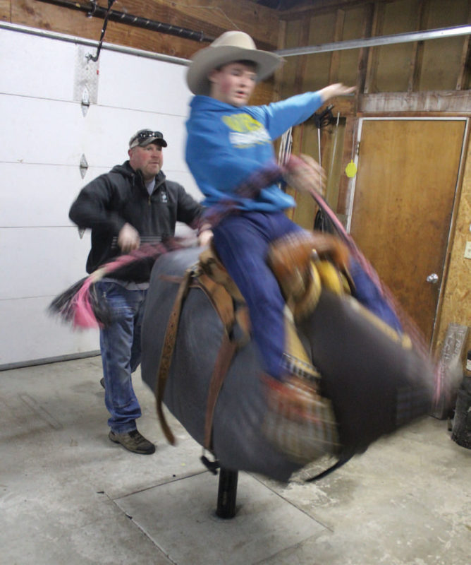 Mason Stuller practicing bull riding at his home on a mechanical bull