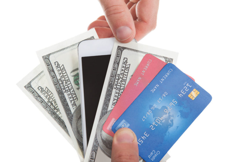 hand holding phone, credit cards, and cash