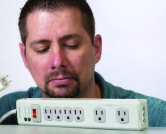Photo of man looking down at a surge protection strip in front of him