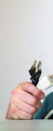 Photo of a hand holding two power plugs