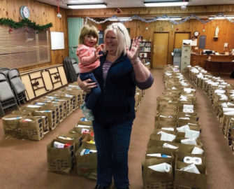 Susan holding a young girl, surrounded by bags full of supplies.